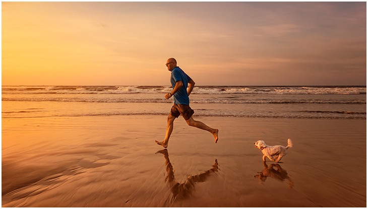 A man runs along the beach with a dog